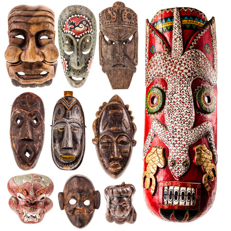 artifact: a collection of different tribal ethnic ancient wooden masks from around the world isolated over a white background Stock Photo