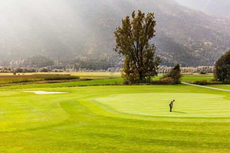 the beautiful vibrant putting green of an Austrian golf course on a sunny day