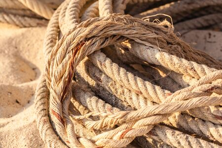 coiled rope: an old coiled rope on the sand of a tropical beach