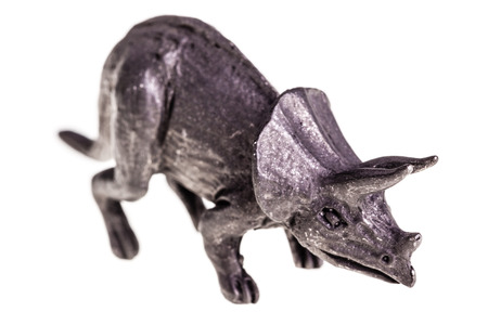 triceratops: a metal triceratops figurine isolated over a white background