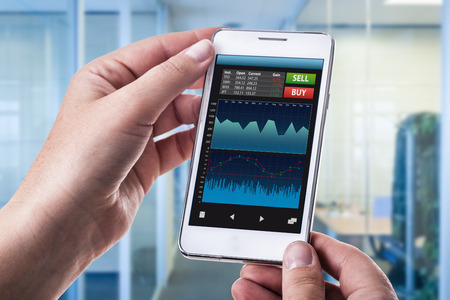 trade: a woman holding a smart phone running a trading or forex app with charts and data