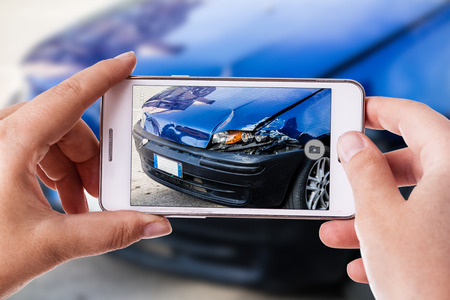 a woman using a smart phone to take a photo of the damage to her car caused by a car crash Stockfoto