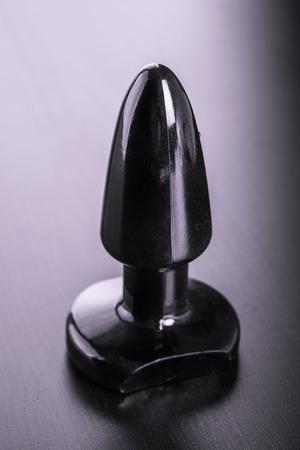 sex toy: a black butt plug rubber dildo over a dark reflective surface