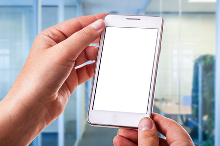 a woman holding a smart phone with a blank white screen on the workplace Stockfoto