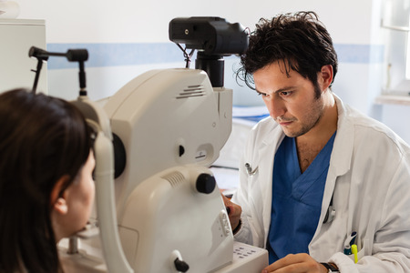 Een jonge oogarts met een niet-mydriatische retinale camera op een meisje Stockfoto - 39557527