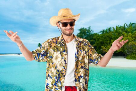 endorsing: a young, attractive male in a colorful outfit in a tropical island setting as a stereotype tourist Stock Photo