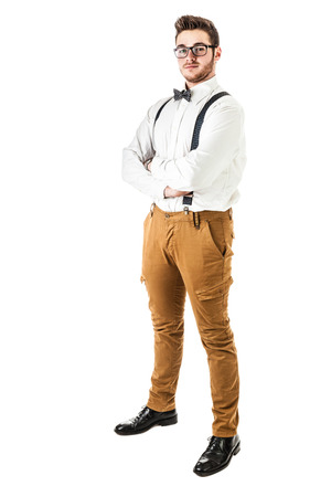 a handsome young man or hipster with braces and a bow tie isolated over a white background