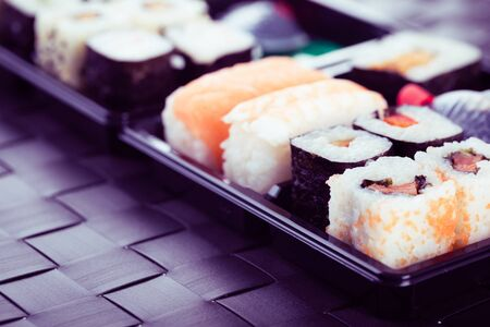 bento box: a sushi box or bento box with assorted sushi pieces over a dark black lunch mat