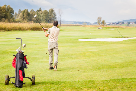 caddie: a golf player making a swing on a vibrant beautiful golf course Stock Photo