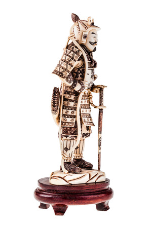 asian warrior: an ancient precious ivory japanese samurai warrior figurine isolated over a white background