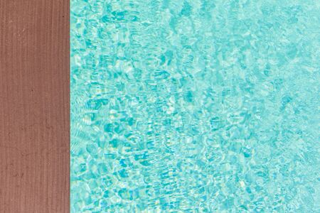 aqua background: wooden planks at the pool side with vibrant pool water