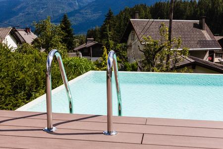 pool bars: Grab bars ladder in blue swimming pool in a garden in Austria Stock Photo