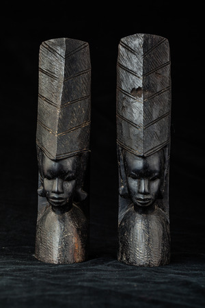 ladies bust: an ancient african black wood carved artifact isolated over a black background