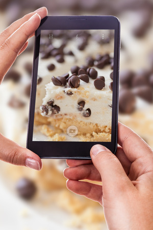 a woman using a smart phone to take a photo of a delicious cake