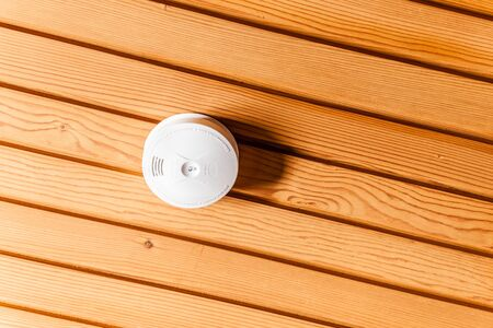 wooden  ceiling: a white smoke detector attached to a wooden ceiling