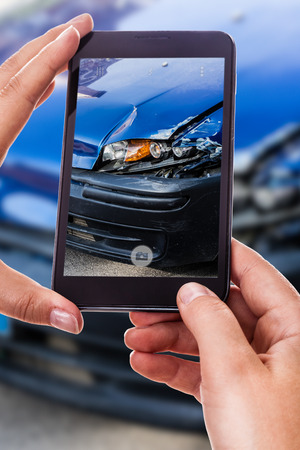 a woman using a smart phone to take a photo of the damage to her car caused by a car crash Foto de archivo