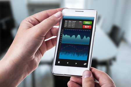 a woman holding a smart phone running a trading or forex app with charts and data