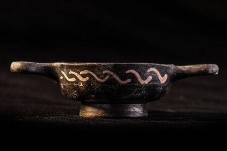 daunia: Apulian black pottery ancient canosan bowl over a dark background Stock Photo