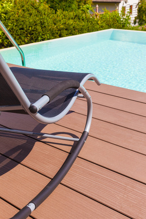 pool side: a chaise lounge on the pool side made of wooden planks Stock Photo