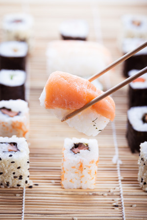 sushi chopsticks: a salmon nigiri sushi being picked up with chopsticks with different types of maki sushi pieces on a wooden sushi mat in the background Stock Photo
