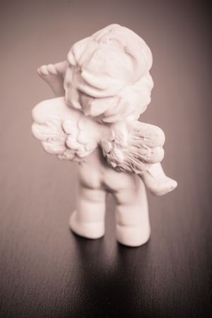 engel: a small cute ceramic angel statuette over a dark surface Stock Photo