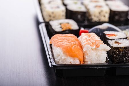 bento box: a sushi box or bento box with assorted sushi pieces over a dark wooden surface Stock Photo