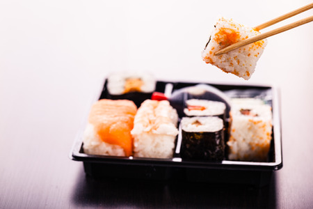 a sushi box or bento box with assorted sushi pieces over a dark wooden surface Stockfoto
