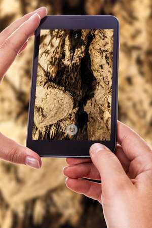 castellana: a woman using a smart phone to take a photo of the interior of a natural cave Stock Photo