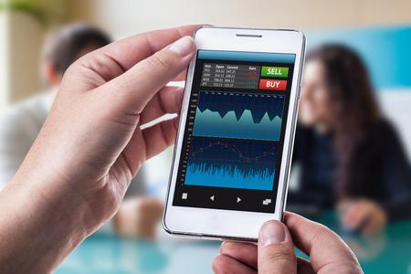broker: una mujer que sostiene un teléfono inteligente que ejecuta una aplicación de comercio o de divisas con gráficos y datos