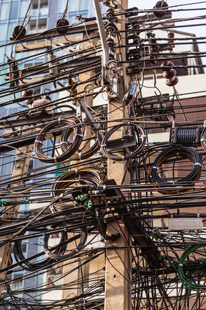 telephone pole: very messy electricity or telephone pole in bangkok, thailand