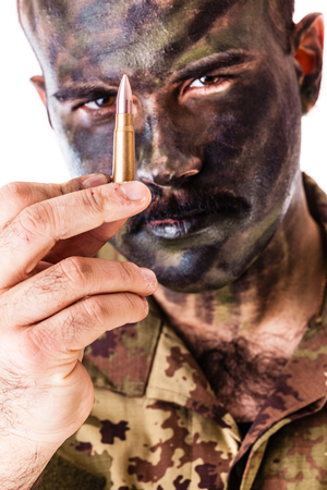 marksman: a marksman or sharpshooter wearing army camouflage face paint and holding a bullet isolated over a white background