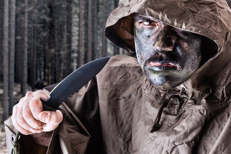 guerrilla warfare: a soldier wearing a poncho o raincoat and army camouflage face paint in a dark wood or forest