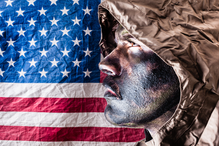 soldado: un soldado que llevaba un poncho o impermeable y camuflaje del ej�rcito cara de pintura sobre la bandera americana Foto de archivo