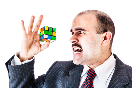rubik: portrait of a businessman trying to solve a cube puzzle isolated over a white background Stock Photo
