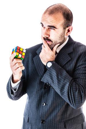 portrait of a businessman trying to solve a cube puzzle isolated over a white background Stock Photo