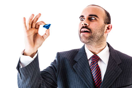 ostentatious: portrait of a classy businessman holding a big blue sapphire isolated over a white background