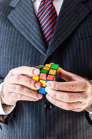 rubik: a puzzled businessman trying to solve a puzzel cube