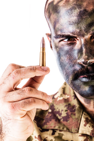 face paint: a marksman or sharpshooter wearing army camouflage face paint and holding a bullet isolated over a white background