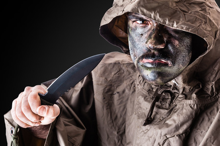 guerrilla warfare: a soldier wearing a poncho or raincoat and army camouflage face paint Stock Photo