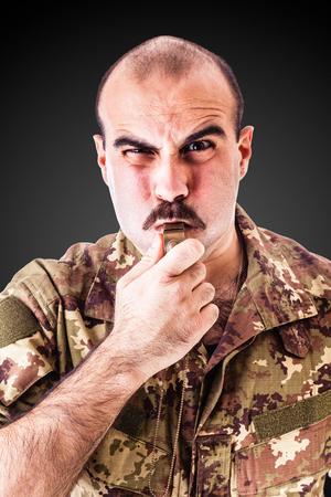 暗い背景に笛を吹く兵士またはドリル軍曹
