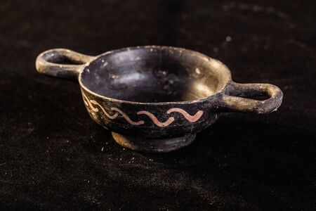 daunia: Apulian black pottery ancient canosan bowl over a dark background Stock Photo