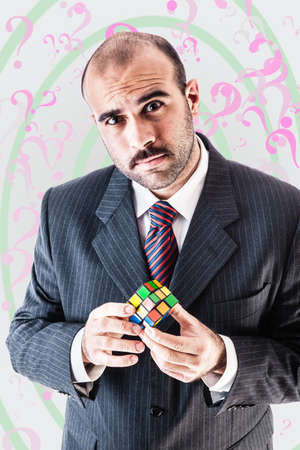 solve: a puzzled businessman trying to solve a puzzel cube