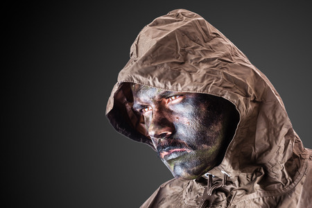 army face: a soldier wearing a poncho or raincoat and army camouflage face paint Stock Photo