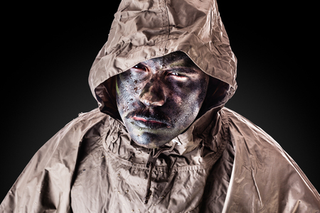face paint: a soldier wearing a poncho or raincoat and army camouflage face paint Stock Photo