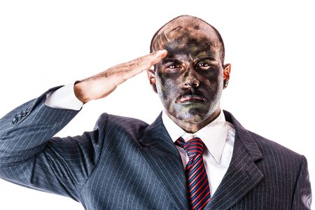 face paint: a businessman wearing a suit and camouflage army face paint saluting isolated over a white background Stock Photo