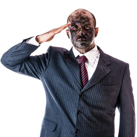 army face: a businessman wearing a suit and camouflage army face paint saluting isolated over a white background Stock Photo
