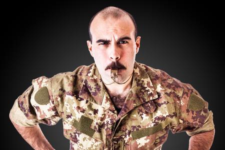 een soldaat of drill sergeant een fluitje blazen op een donkere achtergrond Stockfoto