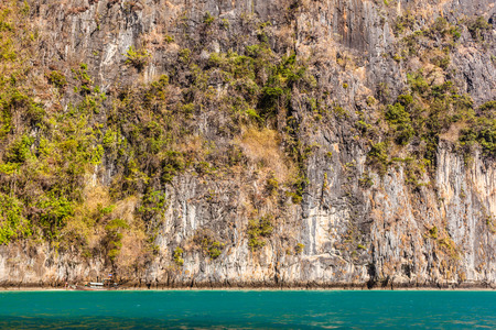 prehistorical: a steep and majestic rockface cliff in the ocean in thailand Stock Photo