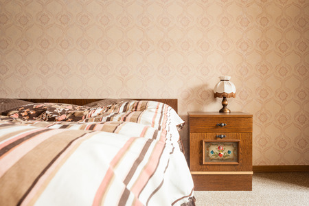 bedspread: a retro styled bed and bedside table in a vintage room