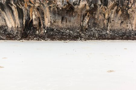 rock strata: white tropical sand on a exotic island beach closed by a vertical rock wall